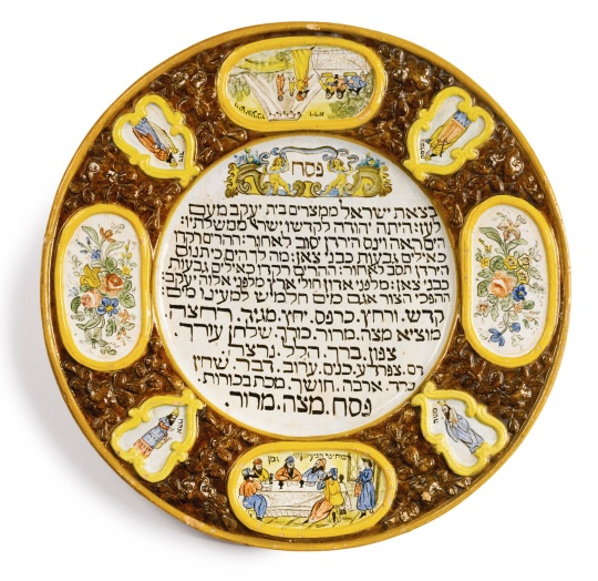 AN ITALIAN MAJOLICA PASSOVER PLATE The center with the Kiddush and the order of the Seder, surrounded by wide molded rim with scenes of Joseph Greeting his Brothers and the Passover Meal in Egypt, four heroes (Moses, Aaron, Solomon, David), and two floral plaques in molded borders, late 19th century.