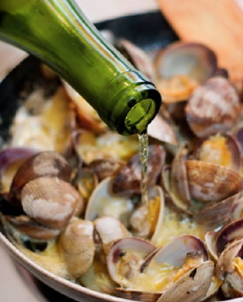 Adding just a splash of white wine to a pan of littleneck clams being simmered in butter, garlic, shallots and cream. Shallow dof, focus on the wine and clams in the front.