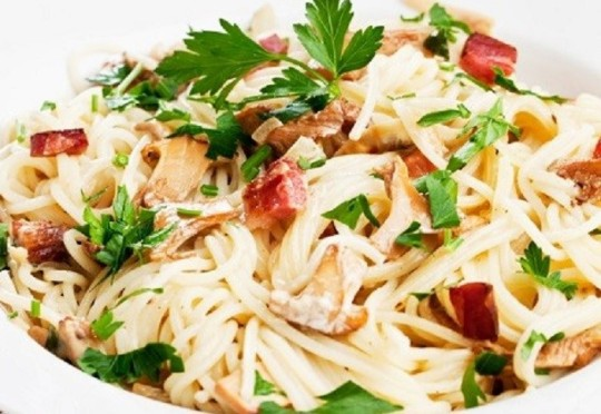 spaghetti with creamy sauce with chanterelle, bacon and parsley